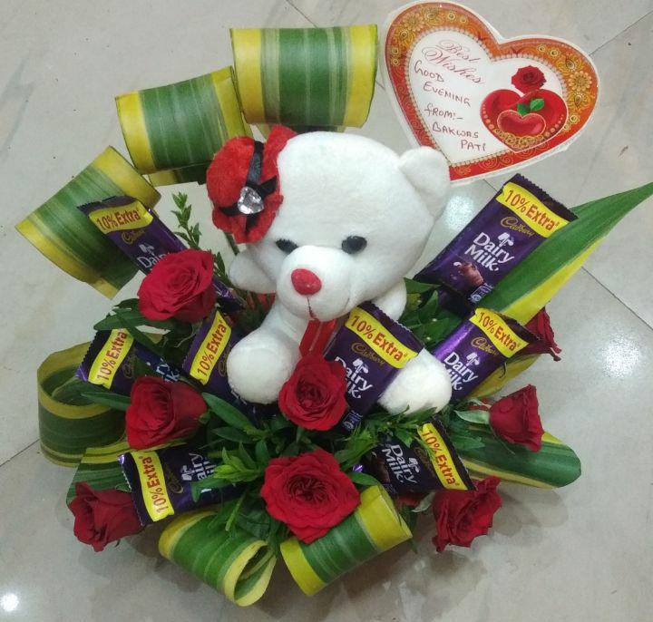 Creative flower arrangement with teddy and chocolates